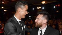 Bintang Real Madrid, Cristiano Ronaldo, berbincang dengan striker Barcelona, Lionel Messi, saat acara penghargaan pemain terbaik FIFA 2017 di London, Senin (23/10/2017). (AFP/Ben Stansall)