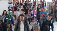 Penumpang membawa barang mereka usai turun dari kereta api jurusan Jawa Tengah tiba di Stasiun Senen, Jakarta, Rabu (28/6). (Liputan6.com/Angga Yuniar)