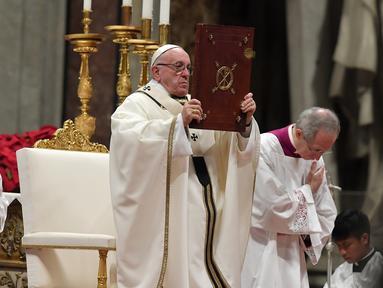 Paus Fransiskus memegang kitab Injil saat memimpin misa Natal di Basilika Santo Petrus, Vatikan, (24/12). Paus menyerukan kepada masyarakat di negara maju agar menjalani kehidupan yang sederhana dan tidak terlalu materialistis. (AFP Photo/Tiziana Fabi)