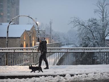 Seorang wanita berjalan-jalan dengan seekor anjing di tengah salju di Milan, Italia (28/12/2020). Hujan salju mengguyur Milan pada Senin (28/12). (Xinhua/Daniele Mascolo)