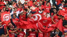 Pendukung Timnas Tunisia mengibarkan bendera dan meneriakan yel-yel saat menyaksikan pertandingan antara Tunisia melawan Libya di kualifikasi Piala Dunia 2018 di Stadion Olimpiade Rades, Tunisia (11/11). (AFP Photo/Fethi Belaid)