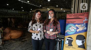 Sales promotion girls mengenakan pelindung wajah dan membawa alat pengukur suhu tubuh di Mall Hewan Qurban Haji Doni, Depok, Jawa Barat, Rabu (8/7/2020). Mall Hewan Qurban Haji Doni memberlakukan protokol kesehatan untuk mengantisipasi penyebaran virus corona COVID-19. (Liputan6.com/Faizal Fanani)