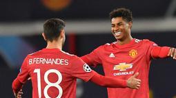 Striker Manchester United, Marcus Rahford merayakan gol bersama Bruno Fernandes dalam lanjutan Liga Champions 2020/2021 di grup H saat menghadapi RB Leipzig di Stadion Old Trafford, Kamis (29/10/2020) dini hari WIB. Manchester United menang 5-0 atas RB Leipzig. (AFP/Anthony Devlin).