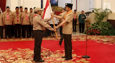 Presiden Joko Widodo (kanan) memberikan bendera Merah Putih kepada Kontingen Gerakan Pramuka Indonesia saat upacara pelepasan di Istana Negara, Jakarta, Jumat (19/7/2019). Pramuka Indonesia akan terbang ke Virginia Barat untuk menghadiri Jambore Pramuka Dunia XXIV. (Liputan6.com/Angga Yuniar)