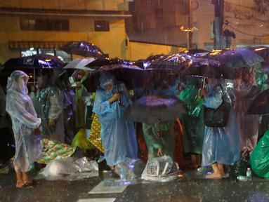 Sejumlah orang memakai jas hujan dan memegang payung demi menghadiri upacara kremasi Raja Thailand Bhumibol Adulyadej di Bangkok, Selasa (24/10). Upacara pemakaman sendiri akan berlangsung selama lima hari mulai Kamis, 26 Oktober 2017. (AP/Sakchai Lalit)