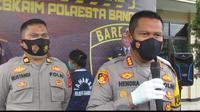 Tersangka DR tampak berada di belakang Kapolresta Bandung, Kombes Pol Hendra Kurniawan, di Mapolresta Bandung, Senin (8/2/2021). (Liputan6.com/ Dikdik Ripaldi)