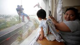 Petugas pembersih kaca berkostum superhero bergelantungan di luar jendela untuk menghibur pasien anak di rumah sakit anak-anak di Guadalupe, Meksiko, 30 April 2019. Pemandangan tidak biasa ini membuat para pasien anak di rumah sakit tersebut terkesima. (REUTERS/Daniel Becerril)
