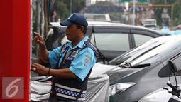 Petugas melakukan pembayaran pada mesin parkir meter di Jalan Falatehan, Jakarta, Selasa (1/11). Pemerintah sudah menggaungkan gerakan nasional nontunai (GNNT) kurang lebih sejak tiga tahun terakhir. (Liputan6.com/Immanuel Antonius)
