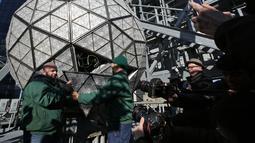 Awak media melihat pekerja menyelesaikan pemasangan bola kristal di atas sebuah gedung di Times Square, New York, Kamis (27/12). Menyaksikan bola kristal raksasa adalah tradisi yang tidak terlewatkan setiap perayaan tahun baru sejak 1907. (AP/Seth Wenig)