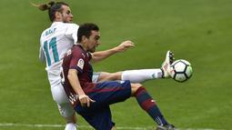 Striker Real Madrid, Gareth Bale, berebut bola dengan gelandang Eibar, Gonzalo Escalante, pada laga La Liga di Stadion Ipurua, Sabtu (10/3/2018). Eibar takluk 1-2 dari Real Madrid. (AP/Alvaro Barrientos)