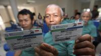 Warga Indonesia sedang melihatkan kartu BPJS Kesehatan