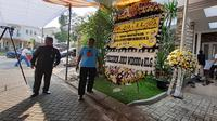 Karangan bunga dari Jokowi di depan rumah almarhum Sutopo Purwo Nugroho di Raffles Hills, Depok, Jawa Barat, Minggu (7/7/2019). (Merdeka.com/Hari Ariyanti)