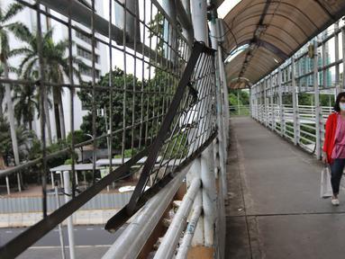Pejalan kaki melintasi jembatan penyeberangan orang (JPO) di Jalan Sudirman, Jakarta, Jumat (27/4).  Pemprov DKI Jakarta akan merevitalisasi 12 JPO di sepanjang Jalan Sudirman dan Jalan MH Thamrin. (Liputan6.com/Arya Manggala)