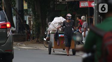 Pemulung melintas di Jalan Raden Saleh, Jakarta, Kamis (30/4/2020). Setiap Ramadan tiba, kemunculan pemulung yang membawa gerobak marak terjadi. Saat ini, kemunculan mereka menjadi masalah tersendiri di tengah upaya memutus mata rantai penyebaran Covid-19. (Liputan6.com/Helmi Fithriansyah)