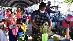 Seorang pria yang mengenakan masker menyiapkan minuman kelapa di pasar menjelang berbuka puasa selama bulan suci Ramadan di Provinsi Narathiwat, Thailand, Selasa (5/5/2020). Ramadan kali ini berlangsung di tengah bayang-bayang virus corona COVID-19. (Madaree TOHLALA/AFP)