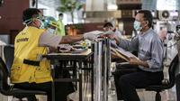 Petugas melayani calon penumpang di Terminal 3 Bandara Soekarno-Hatta, Tangerang, Banten, Senin (11/5/2020). Beberapa maskapai mulai membuka layanan penerbangan setelah Kementerian Perhubungan kembali membuka izin layanan transportasi umum pada Kamis lalu. (Liputan6.com/Faizal Fanani)