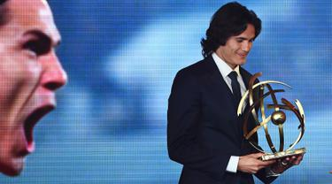 Penyerang PSG, Edinson Cavani memegang trofi Pemain Terbaik Liga Prancis pada upacara penghargaan yang digelar UNFP di Paris, Senin (15/5). Penghargaan ini jadi yang pertama untuk Cavani sejak datang ke Prancis 2013 silam. (FRANCK FIFE/AFP)