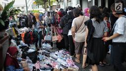 Sejumlah pedagang kaki lima (PKL) memadati trotoar dan badan jalan kawasan Kota Tua, Jakarta, Kamis (27/12). Keberadaan PKL mengganggu ketertiban dan kelancaran lalu lintas orang dan kendaraan. (Liputan6.com/Faizal Fanani)