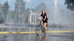 Seorang pesepeda melewati semprotan air di Schwarzenbergplatz di Wina, Austria (28/7/2020). Suhu tertinggi di Wina mencapai angka 37,2 derajat Celsius pada Selasa (28/7). (Xinhua/Guo Chen)