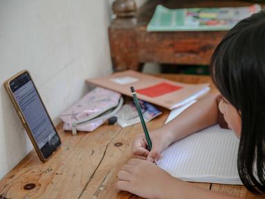 Seorang siswi memperhatikan ponsel saat belajar secara daring di Jakarta, Rabu (4/11/2020). Federasi Serikat Guru Indonesia merekomendasikan sejumlah usulan kepada Kementerian Pendidikan dan Kebudayaan untuk mengubah sistem Pembelajaran Jarak Jauh. (Liputan6.com/Faizal Fanani)