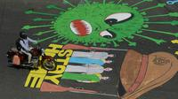 Pengendara motor melewati melewati grafiti virus corona yang dilukis di jalan selama penerapan lockdown nasional di Chennai, India, Senin (13/4/2020). Grafiti itu dibuat untuk meningkatkan kesadaran warga yang keluyuran keluar rumah saat lockdown karena pandemi virus corona. (Arun SANKAR/AFP)