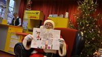 Pria berkostum Sinterklas menunjukkan hadiah lukisan dari seorang anak di Kantor Pos Natal di Himmelpfort, Jerman, 19 Desember 2018. Anak-anak di seluruh dunia mulai mengirim surat berisi permohonan kepada sinterklas di kantor pos itu (Tobias SCHWARZ/AFP)