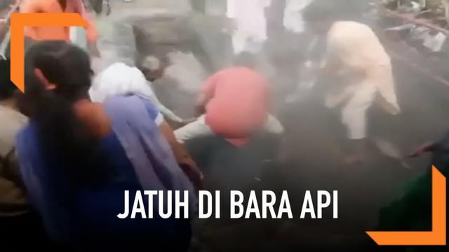 Seorang wanita menjalani ritual kuno di India. Di pertengahan jalan wanita tersebut jatuh di bara api. Ritual ini menandai dimulainya festival Holi.