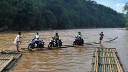 Sebuah rakit mengangkut motor dan warga menyeberangi Sungai Cisadane di Rumpin, Bogor, Selasa (13/3). Mereka terpaksa menaiki rakit akibat jembatan Gerendong yang merupakan akses jalan utama Ciseeng -Rumpin masih dalam perbaikan. (Merdeka.com/Arie Basuki)