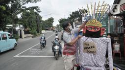 Warga memasangkan masker pada ondel-ondel di depan pintu masuk permukiman RT 12 RW 14, Cipinang Besar Utara, Jakarta, Kamis (16/4/2020). Warga secara swadaya membuat ondel-ondel tersebut sebagai upaya mengajak masyarakat melindungi diri dari penyebaran Covid-19. (merdeka.com/Iqbal S. Nugroho)