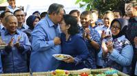 Ketua Umum Partai Demokrat Susilo Bambang Yudhoyono mencium istrinya, Ani Yudhoyono saat potong tumpeng dalam perayaan HUT Partai Demokrat ke-16 di Cikeas, Jawa Barat, Sabtu (9/9). (Liputan6.com/Angga Yuniar)