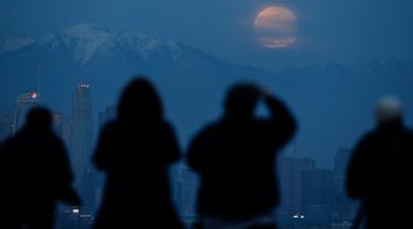 Orang-orang menyaksikan fenomena supermoon atau bulan super dengan latar belakang pusat kota Los Angeles dari Kenneth Hahn Park, Minggu (20/1). Supermoon akhir pekan ini adalah yang pertama terjadi pada tahun 2019 ini. (AP/Ringo H.W. Chiu)