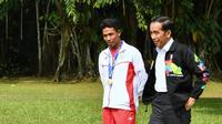 Presiden Joko Widodo atau Jokowi (kanan) dan sprinter Lalu Muhammad Zohri (kiri) berjalan santai di Istana Bogor, Jawa Barat, Rabu (18/7). Jokowi berpesan kepada Zohri agar tak lekas berpuas diri. (Liputan6.com/Pool/Biro Pers Setpres)