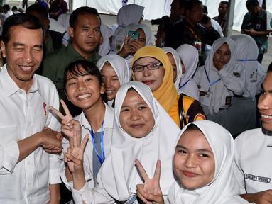Presiden Joko Widodo berfoto bersama sejumlah siswa saat acara penyerahan KIP dan PKH di Kota Banjarbaru, Kalimantan Selatan (26/3). (Liputan6.com/Pool/Biro Setpres)
