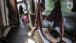Seorang anak tertidur di atas ayunan buatan di permukiman padat penduduk di kawasan Cakung, Jakarta, Senin (15/2/2021). Jika dibandingkan dengan September 2019, jumlah penduduk miskin di perkotaan naik 1,32 persen, sedangkan di perdesaan naik 0,60 persen. (merdeka.com/Iqbal S Nugroho)
