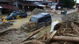 Mobil-mobil terjebak lumpur di daerah yang terkena banjir bandang di Masamba, Sulawesi Selatan, Rabu (15/7/2020). Banjir bandang akibat tingginya curah hujan tersebut mengakibatkan 16 orang meninggal dunia dan puluhan warga dilaporkan masih dalam pencarian. (AP/Khaizuran Muchtamir)