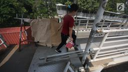 Pejalan kaki melewati lubang di atas JPO di Halte Bus Transjakarta di Jembatan Gantung, Cengkareng, Jakarta, Jumat (27/7). JPO yang rusak akibat tertabrak truk sejak setahun lalu hingga kini belum diperbaiki.  (Liputan6.com/Arya Manggala)