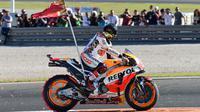Pembalap Spanyol Repsol Honda, Marc Marquez membawa bendera di atas motor setelah memenangkan balapan seri ke 18 MotoGP Grand Prix Valencia di Sirkuit Ricardo Tormo, Valencia (12/11). Marc Marquez finis di urutan ketiga. (AFP PHOTO / Jose Jordan)