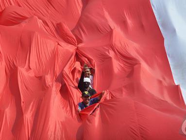 Sejumlah relawan membentang bendera Merah Putih raksasa saat mengikuti kirab budaya, Jakarta, Senin (20/10/2014) (Liputan6.com/Miftahul Hayat)
