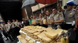 Sejumlah petugas kepolisian memperlihatkan barang bukti narkoba jenis ganja, Jakarta, Jumat (13/2/2015). Satuan Narkoba Polres Metro Jakarta Barat berhasil mengungkap jaringan peredaran ganja lintas Sumatera ke Jakarta. (Liputan6.com/Faizal Fanani)