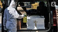 Petugas menyemprotkan disinfektan pada peti jenazah pasien Covid-19 sebelum proses kremasi di Krematorium Cilincing, Jakarta Utara, Minggu (25/7/2021). Setiap harinya petugas mampu melakukan kremasi sebanyak 11 hingga 14 jenazah di tujuh tungku pembakaran yang tersedia. (merdeka.com/Iqbal S Nugroho)