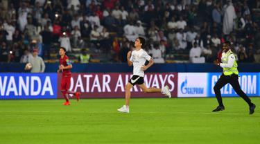Seorang fans Real Madrid berlari menerebos lapangan selama pertandingan semifinal Piala Dunia Antarklub 2018 antara Real Madrid melawan Kashima Antlers di stadion Zayed Sports City di Abu Dhabi, Uni Emirat Arab (19/12). (AFP Photo/Giuseppe Cacace)
