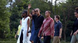 Mantan Presiden AS, Barack Obama mengabadikan gambar dari ponselnya saat berwisata di Candi Borobudur, Magelang, Jawa Tengah, Indonesia, (28/6). Obama mengenakan celana jeans biru dan polo shirt hitam. (AP Photo / Slamet Riyadi)