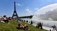 Warga berjemur di samping air mancur di Trocadero Esplanade, dekat Menara Eiffel, Paris (8/5). Kebun Trocadero Esplanade memiliki luas 93.930 meter persegi (23,21 hektar). (AFP Photo/Gerard Julien)