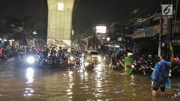 Sejumlah pengendara sepeda motor menunggu banjir surut yang menggenangi kawasan Simpang Seskoal, Kebayoran Lama, Jakarta, Sabtu malam (16/2). Banjir setinggi 50cm - 1 meter hanya bisa dilalui bus atau kendaraan berukuran besar. (Liputan6.com/Septian)