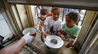Anak-anak yang membutuhkan antre untuk menerima makanan berbuka puasa dari juru masak di dapur Masjid Muslim Sunni Abdel Kader al-Kilani, Baghdad, Irak, 19 April 2021. Kegiatan ini berlangsung selama bulan suci Ramadhan. (AHMAD AL-RUBAYE/AFP)