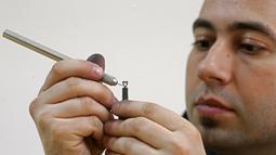 Jasenko Djordjevic saat mengukir ujung pensil menjadi bentuk hati di Tuzla, Bosnia dan Herzegovina, Selasa (26/4). Keterampilan Djordjevic membutuhkan konsentrasi penuh saat membuat ukiran miniatur. (REUTERS / Dado Ruvic)