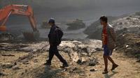 """Penduduk setempat berjalan melewati """"danau lumpur"""" yang mengubur kendaraan dan mesin di tambang giok Myanmar. (AFP)"""