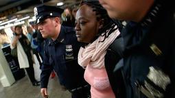 Seorang perempuan tersangka pelaku pendorongan ditangkap petugas NYPD pendorongan di stasiun Time Square, New York, Senin (7/11). Tersangka diidentifikasi sebagai Melanie Liverpool-Turner namun motifnya belum diketahui. (REUTERS/James Carman)