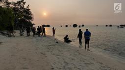 Warga menyaksikan matahari tenggelam (sunset) di Pulau Pari, Kepulauan Seribu, Jakarta pada 3 Agustus 2019. Pulau Pari mempunyai keindahan saat matahari terbenam yang dapat dilihat dari Tanjung Renggae. (Liputan6.com/Herman Zakharia)
