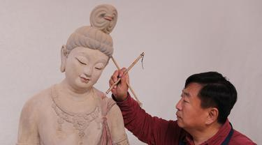 Seniman Du Yongwei mewarnai sebuah patung dengan cat di Dunhuang, Provinsi Gansu, China, Minggu (5/4/2020). Seni patung warna-warni merupakan bentuk kesenian tradisional di Dunhuang. (Xinhua/Du Zheyu)